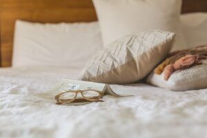 Briller ligger på seng med hvidt betræk