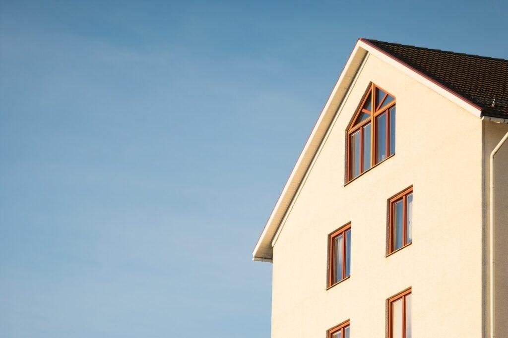 Hvid facade af stor bygning med blå himmel