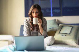 Kvinde i grå drikker kaffe og kigger på computer