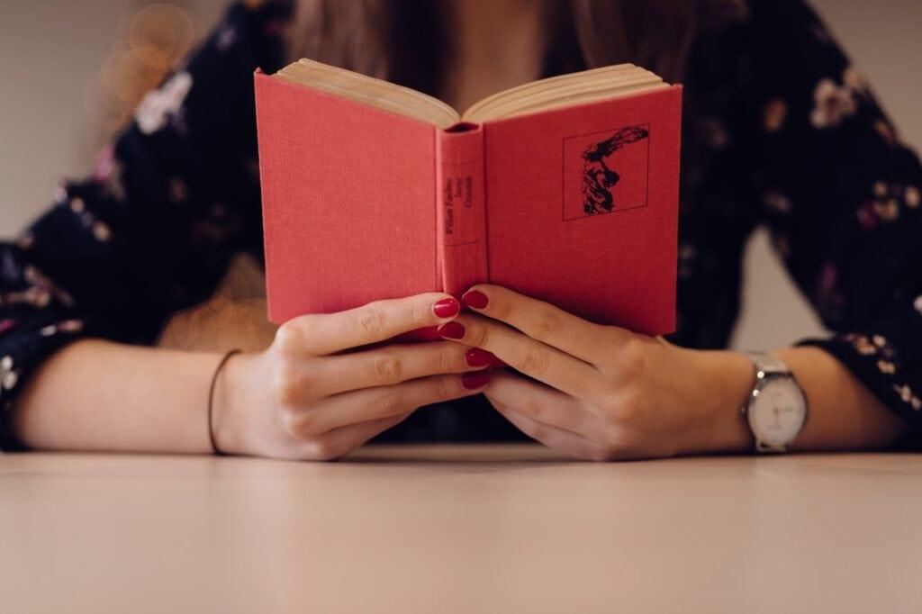 Kvinde læser rød bog med ur på