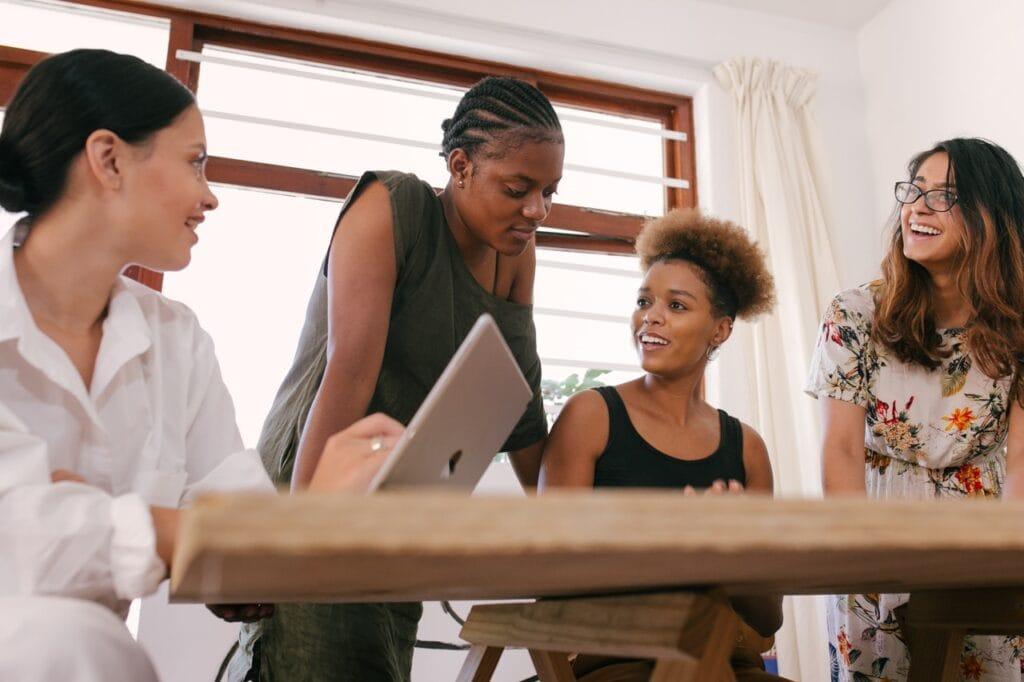 Kvinde taler til møde med tre andre kvinder