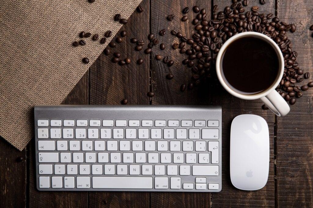 Tastatur og mus på bord med kaffebønner